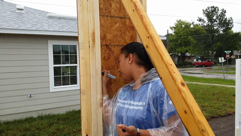 Maria's daughter writes a note of her own on the frame of her new home.  photo credit: Habitat for Humanity