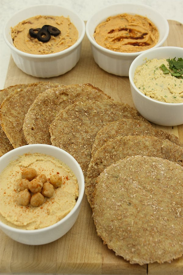 four kinds of hummus with flatbread on board.