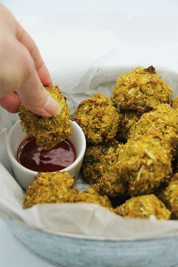 baked veggie balls in basket being dipped into sauce