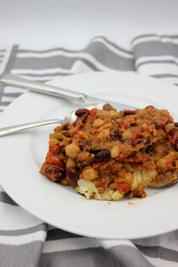 4-bean chili caulicarne over potato on plate.
