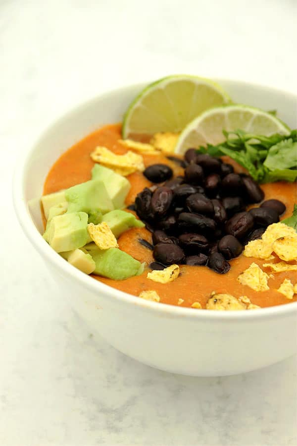 Easy vegan tortilla soup in white bowl with black beans, coriander, lime avocado and tortilla chips on top