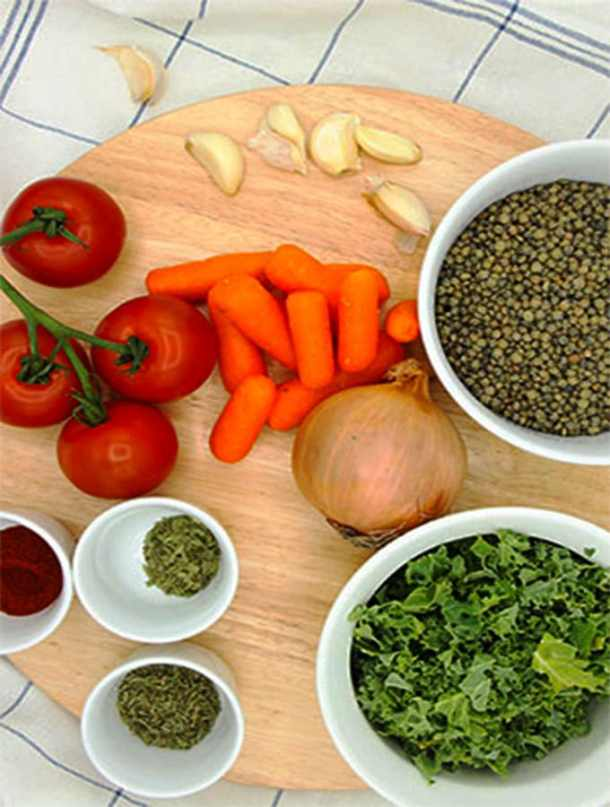 Ingredients for vegan French lentil soup on round wooden board