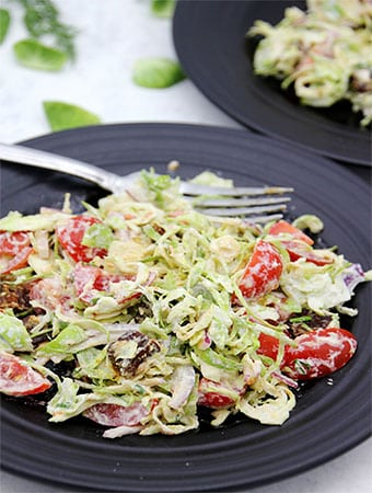 brussels sprouts salad on black plates