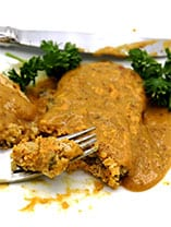 chickpea cutlet with mustard gravy on white plate being cut by fork