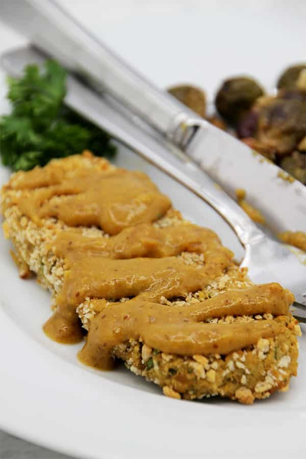 chickpea cutlets with mustard sauce on plate with fork and knife.