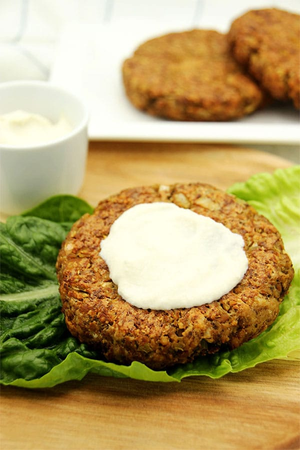 Deluxe tempeh burger on lettuce leaf on wooden plate with cashew aioli on top.