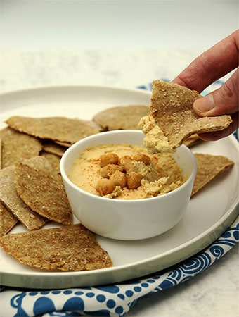 Too easy hummus and flatbread with hand dipping into bowl