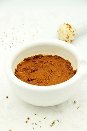 Fresh Thai red curry paste in mortar with pestle in background