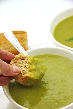 creamy asparagus soup in white bowl with bread being dipped into the bowl.