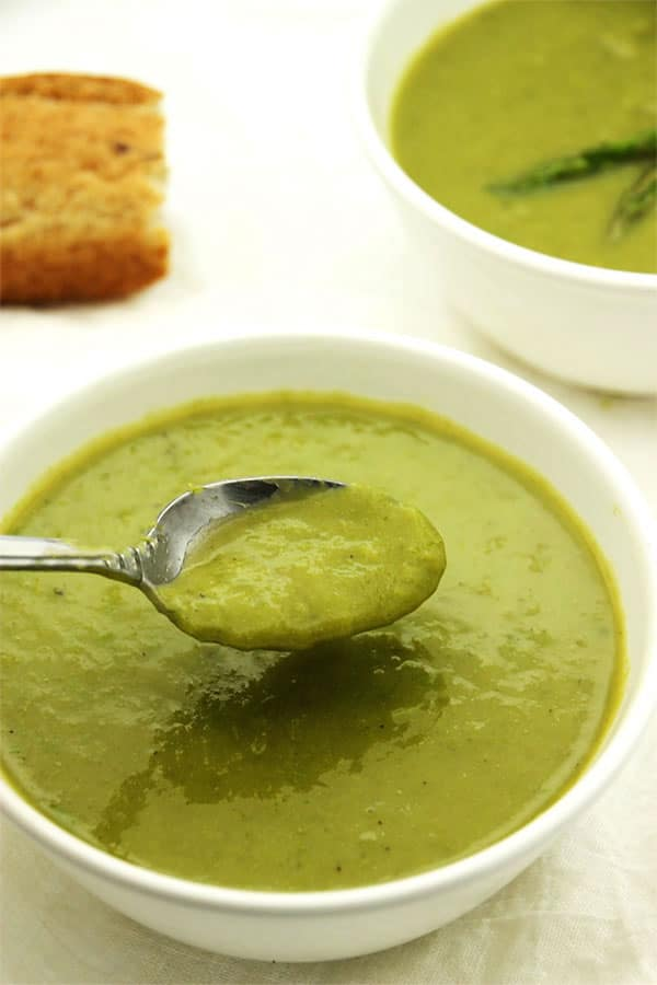 creamy asparagus soup in white bowl with spoon being dipped.