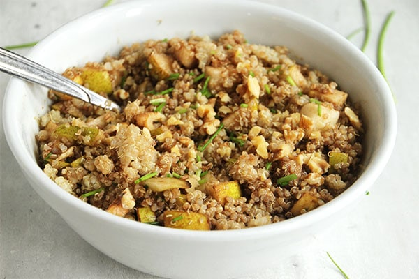 Quick quinoa & pear salad in white bowl with spoon.