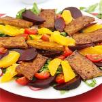 spicy beet orange tofu salad on white plate with red mat.