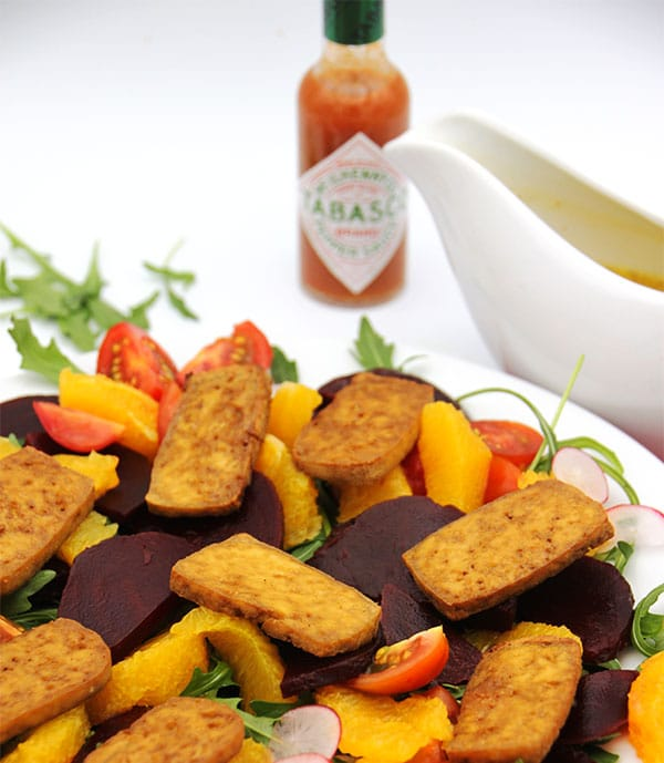 spicy beet orange tofu salad on white plate with dressing and tabasco in background