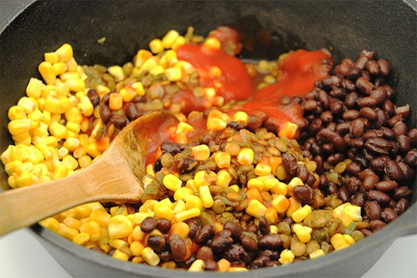 vegan tamale pie filling being cooked with lentils, black beans, corn and tomato sauce
