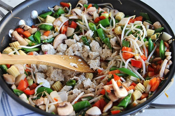 tofu is being added to mixed vegetables in black wok.