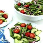 Salad of fresh green beans, cucumber, tomatoes, and red onion in white bowl with blue cloth on table.