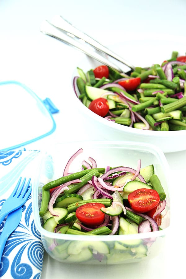 Fresh green bean salad in storage container and in white bowl in background.