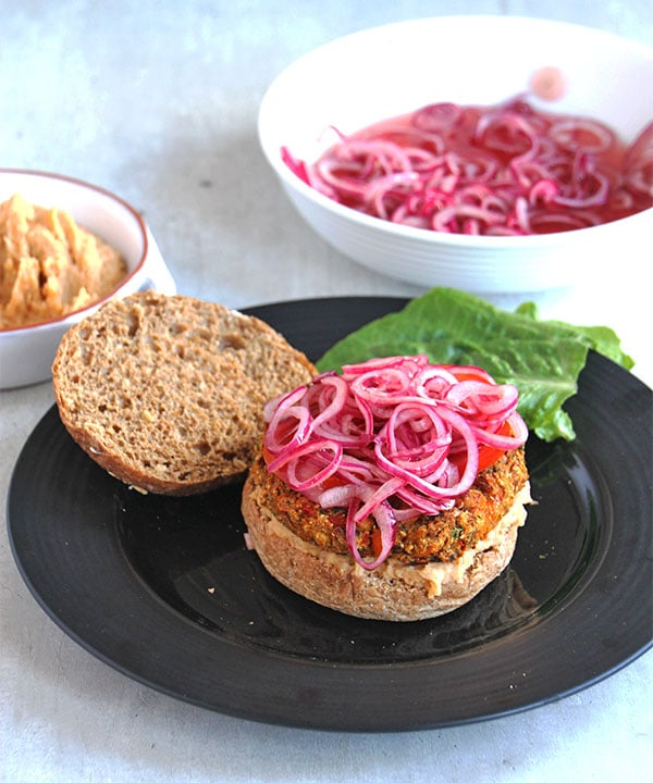 Quick pickled onions are on top of a veggie burger in a bun with the bun top off and the pickled onions in a white bowl in the background.