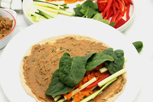 whole wheat wrap with white bean spread on it and courgette, carrots, red pepper and spinach on one end. Ready to roll.