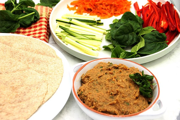 whole wheat wrap on white plate with white bean spread in white bowl and sliced red pepper, spinach, carrots and courgette on plate.