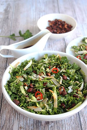 Asian chopped salad with 5-spice almonds and roasted coconut in white bowl with dressing in background.