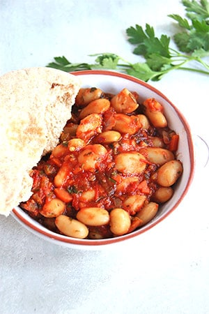 Greek baked beans (Gigantes Plaki) in small white dish with pita bread dipped in the dish.