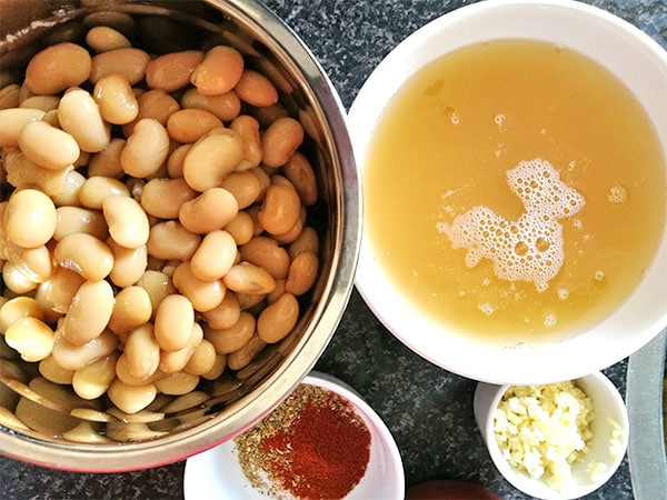 Cooked butter beans, reserved liquid from the beans, minced fresh garlic and mixed spices in white dish all on black counter top.