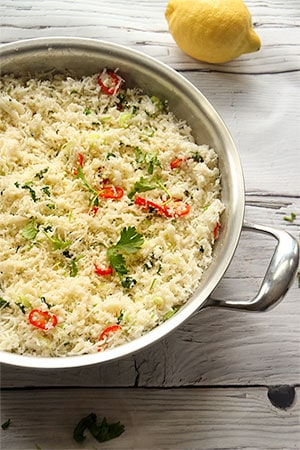 lemon cauliflower rice with red peppers, coriander. lemons and scallions in stainless steel pan on board and whole lemon in background.