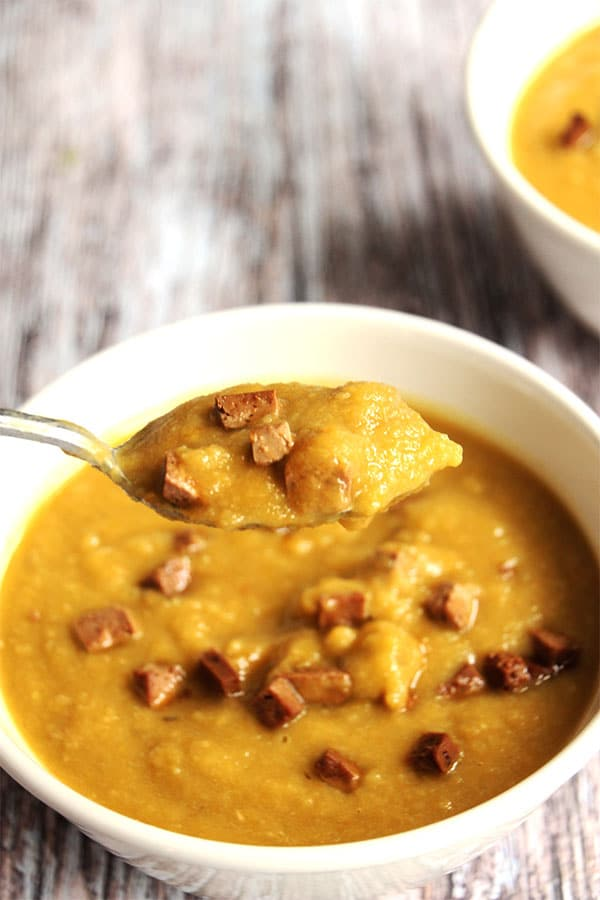 spoonful of smoky split pea soup is being lifted over a white bowl of soup.