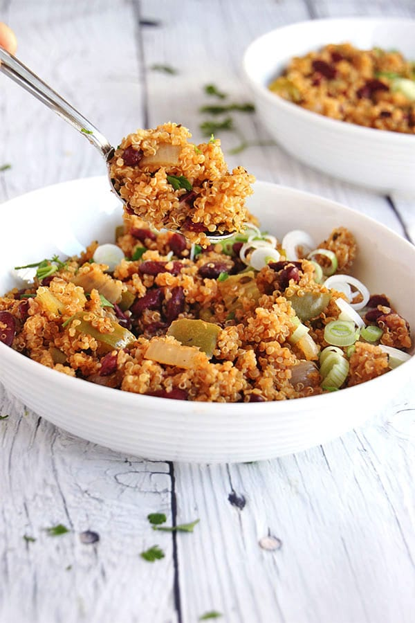 weeknight red beans & quinoa in white bowl with spoonful lifted.