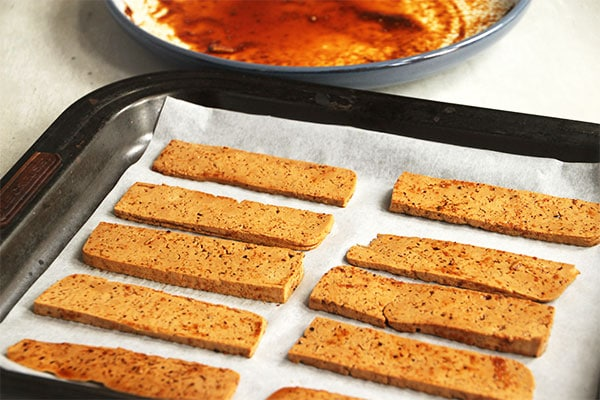 marinated strips of tofu are placed on a parchment-lined baking tray.