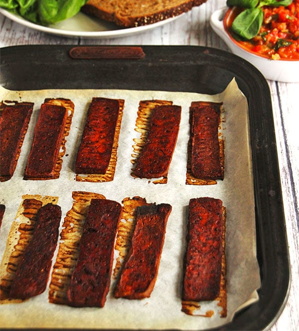 baked tofu bacon strips on baking tray lined with parchment paper.