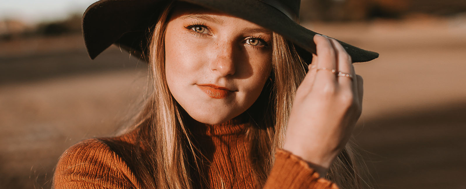 freckled face teenager in sunlight wearing hat
