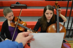 My friend and I practicing for a competition, on the bleachers of a gym, and my mom acting as our impromptu music stand.