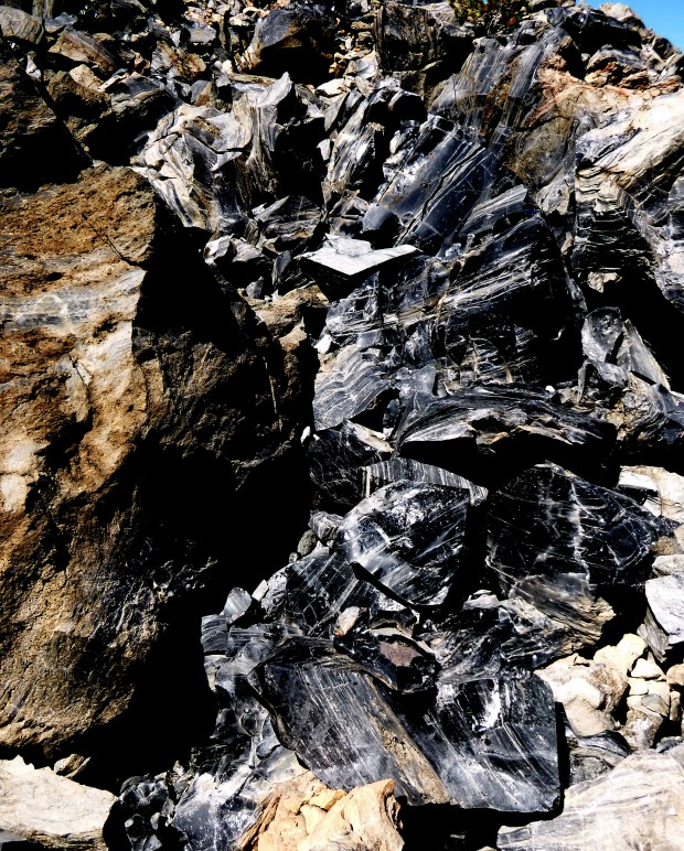 More obsidian with reddish pumice on left, Big Obsidian Flow, Newberry National Volcanic Monument, Oregon