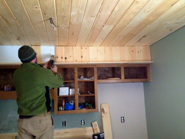Jonathan installing pine facing and shelf above kitchen cabinets