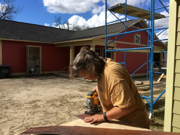 Sandi jigsawing flooring pieces to fit around a door opening