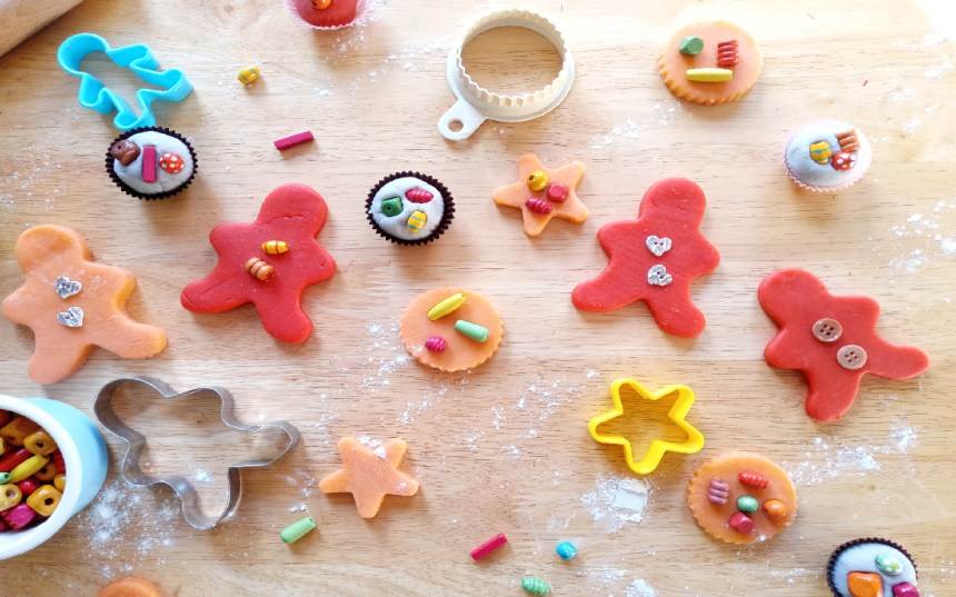On the table are cut out play dough shapes decorated with wooden beads, play dough mini cakes, biscuit cutters and dish of wooden beads.
