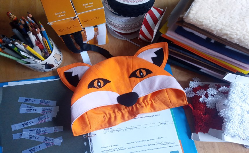 Children's Costume Safety. A table covered with folded pieces of fabric, rolls of lace flowers and ribbons, a file with papers in it, fabric sew in costume labels, the fox hood, two boxes of velcro and a cup full of pens and pencils.
