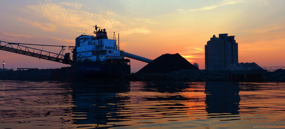 Ship docked at St. Mary's Cement plant at sunset.