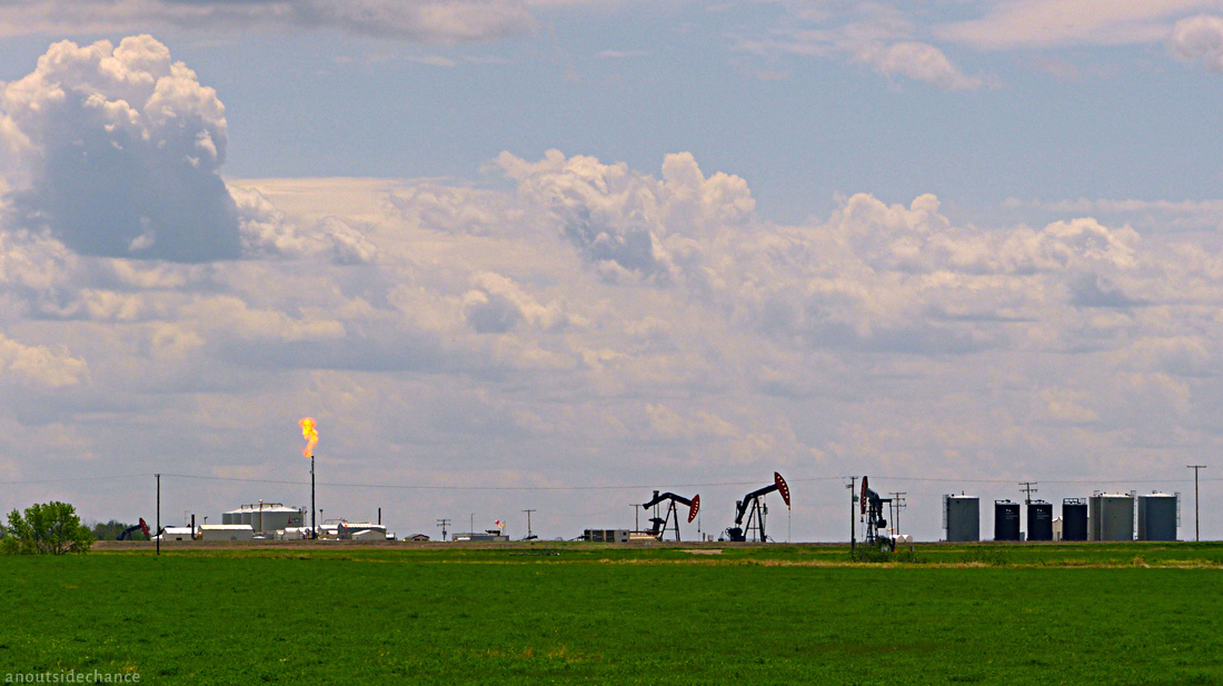 Oil wells with gas flare, southern Saskatchewan.