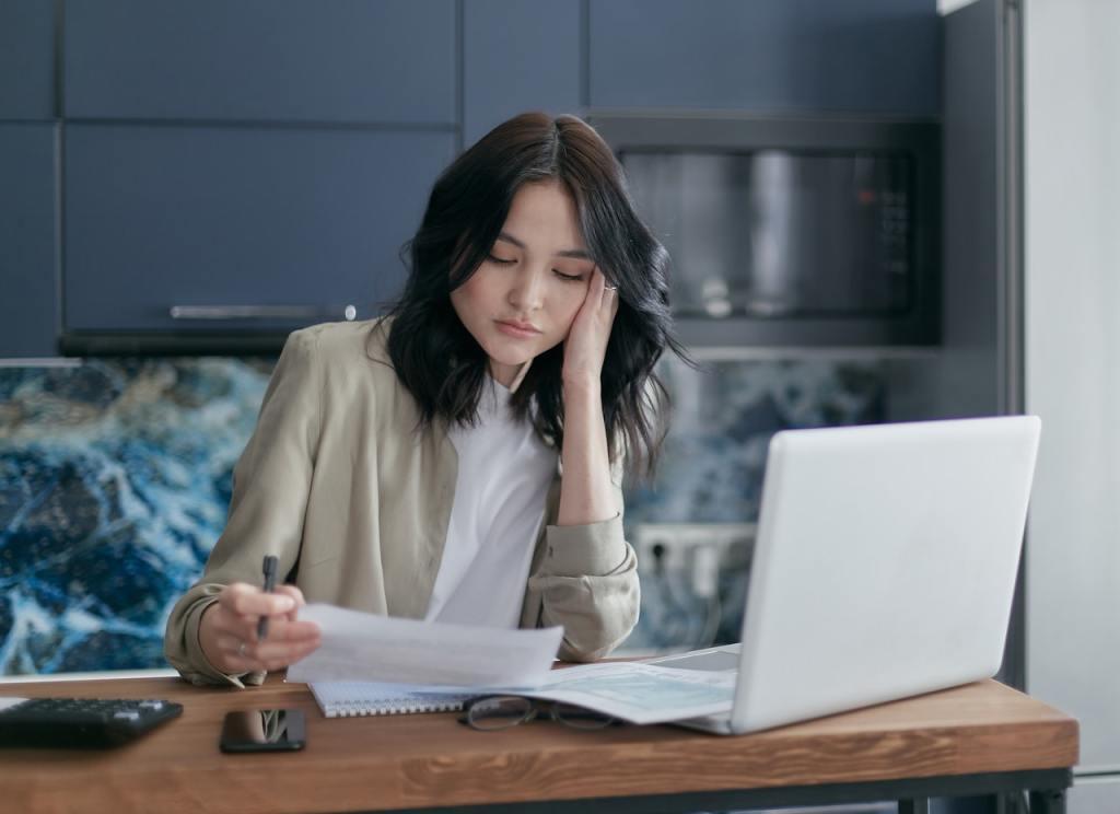 Donna alla scrivania con pc e documenti per calcolare quanto costa di contributi un dipendente