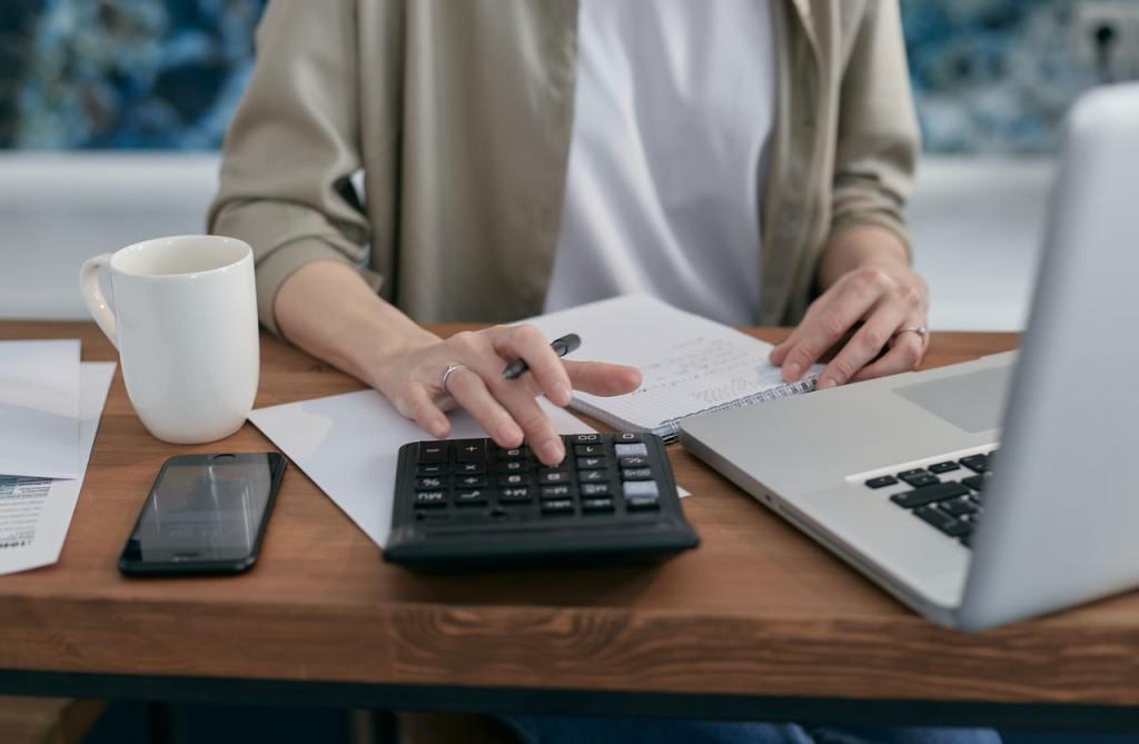 Donna con calcolatrice per calcolare quanto costa di contributi un dipendente