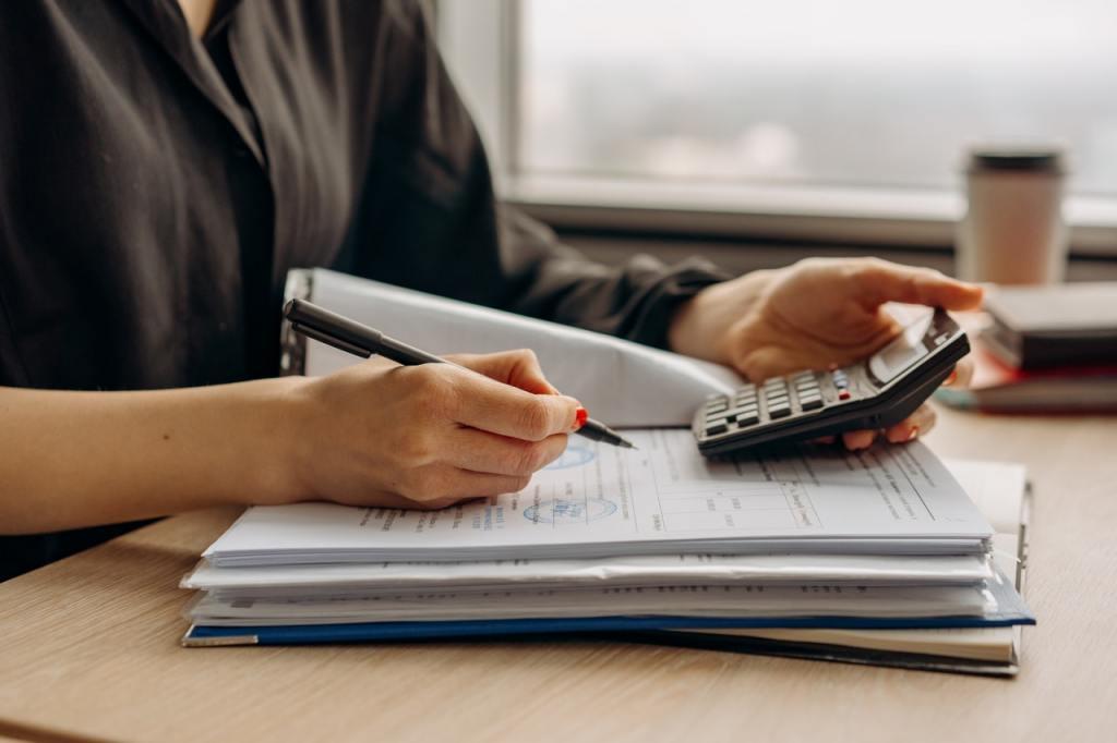 Professionista alla scrivania con documenti e calcolatrice per valutare quanto costa di contributi un dipendente