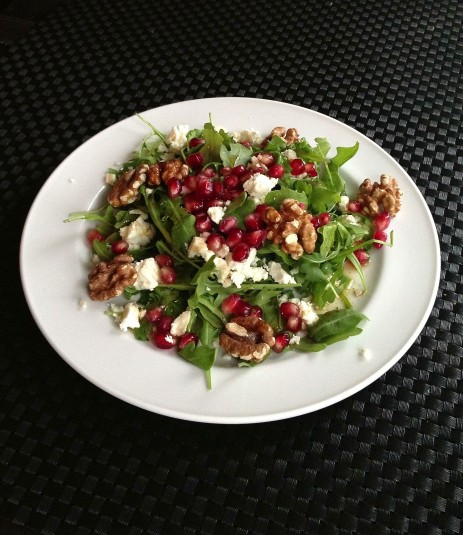 Arugula salad with pomegranate seeds, feta and walnuts