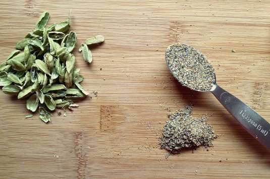 ground green cardamom with empty pods with measuring spoon