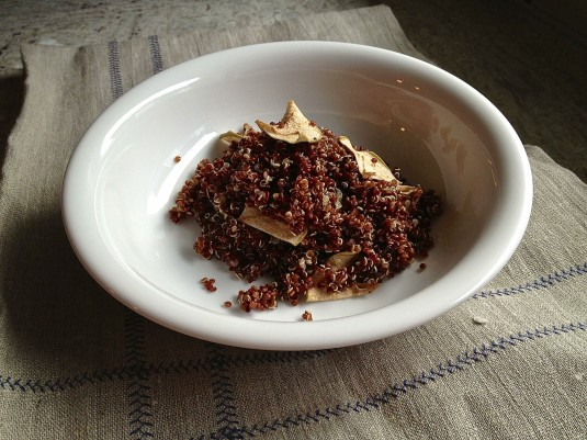 red quinoa in bowl with dried apple slices