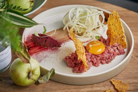 Тартар из говядины с приготовленным в масле теплым желтком, хрустящей моченой антоновкой и винегретом из вяленых томатов и кедровых орехов