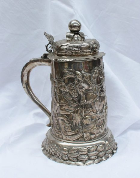 A continental white metal tankard, the domed lid with a fruit finial and embossed with fruit, the cylindrical body embossed with figures on horseback, above a flared footrim, 27cm high approximately 685 grams. Sold for £750 at Anthemion Auctions
