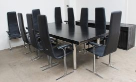 In the style of Arne Jacobsen, a black ash dining table with chrome legs together with a set of ten black leather dining chairs and a matching sideboard. Sold for £650 at Anthemion Auctions